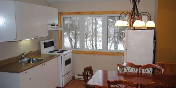 Condo #12: Salon cuisine à aire ouverte, 2 chambres avec lit double, 1 divan lit au salon, salle de bain complète. Bâtiment à côté de la salle c