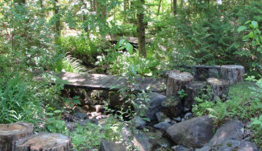 Un ruisseau surplombé de deux ponts traverse le terrain jusqu'au lac.